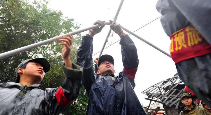 4月23日,震区降雨给灾区群众生活带来不便,战士冒雨为芦山县龙门乡隆兴村村民搭建帐篷。(来源:新华网)