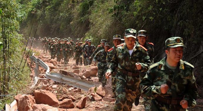 4月20日,因地震造成山体滑坡,道路受阻,救援人员徒步赶往救援现场。(来源:新华网)