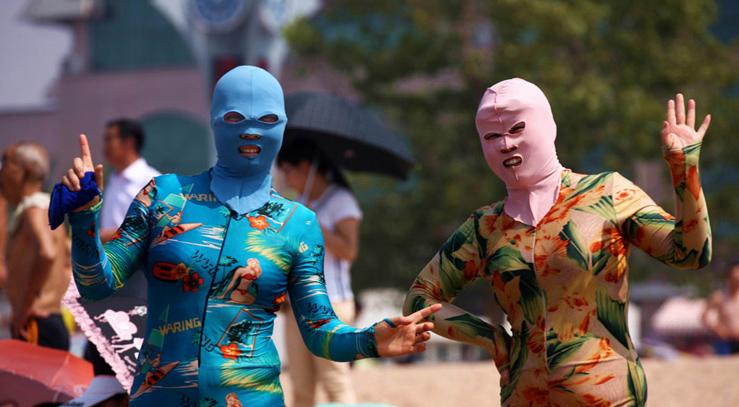 """8月8日,在青岛第一海水浴场万人畅游汇泉湾活动现场的""""比基脸""""大妈,各色防晒利器。"""
