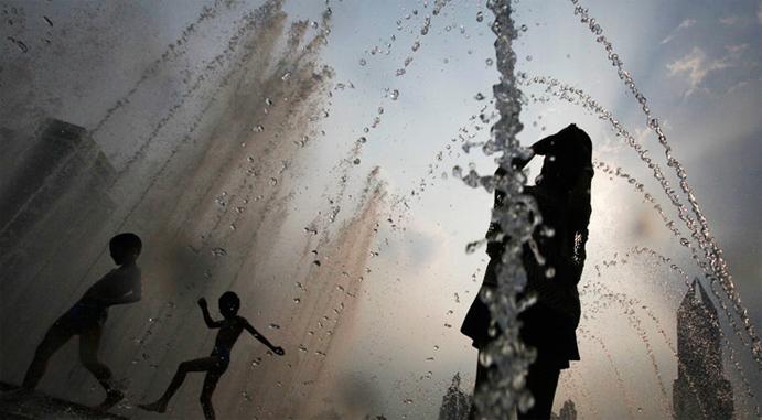 8月7日,上海人民广场,孩子们在喷泉旁玩耍纳凉。