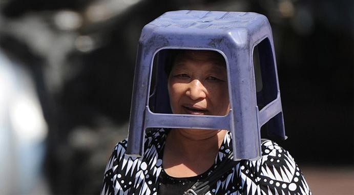 8月7日,重庆一擦鞋大妈用凳子扣头遮阴避暑。