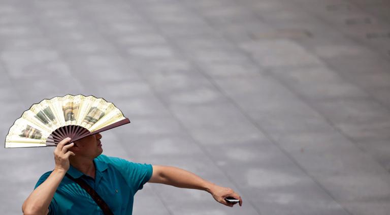8月7日,上海外滩,一名游客打开扇子遮挡阳光。