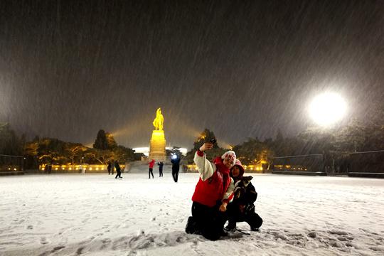 辽宁锦州迎久违降雪 市民雪夜户外嬉戏