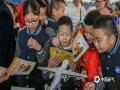 活动现场派发的中小学气象灾害避险指南深受孩子们的欢迎。(摄影/林松 文/黄英伟)