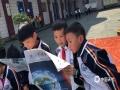 """3月23日迎来世界气象日,贵州省气象部门围绕""""太阳、地球和天气""""的主题举办了丰富多彩的活动,以科普宣传引导公众关心支持气象事业发展。图为同学们认真阅读宣传资料。(李锦文/摄)"""