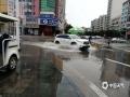 暴雨过后部分路段积水严重,车辆小心涉水通过。(摄/孙活坤)