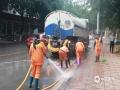 图为环卫工人在清洗大风后狼藉的街道。