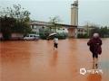 昨天(14日)午后,受强对流云系影响,广东省云浮市新兴县出现雷暴、短时强降水等恶劣天气。由于降水集中,该县出现多处严重积水,影响当地道路交通、学生返校。图为强降水导致当地惠能中学校门被淹,学生涉水返校。(摄影:李玖达)