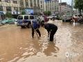 怀集县多路段受浸,政府部门工作人员打开沙井盖排水。