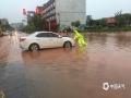 怀集县高铁路口受浸,交警助群众推车出水浸路段。