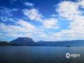 中国天气网讯 站在远处远眺泸沽湖,海天一色,风光旖旎,蓝天白云映衬在绿树碧湖之下,美不胜收。图片4月29日拍摄于泸沽湖。(图/和文武 文/一坤)