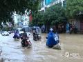 图为11日上午,南丹县城关镇出现内涝,群众出行受阻。(图/杨哲 文/叶小丽 杨哲)