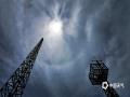 中国天气网讯 14日中午12点左右,南宁天空出现难得一见的日晕景象,五彩的光环笼罩在太阳四周,炫丽多彩。 日晕的形成由于几日的降雨,空气中的水汽含量高,上空形成蕴含冰晶的高云,太阳光经过冰晶时向不同方向发散产生折射和反射,最终在太阳周围形成一个巨大彩色光环。(图文/卢威旭)