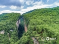 """中国天气网讯 天生桥景区位于贵州省水城县金盆苗族彝族乡的干河地域,属石灰岩洞穴坍塌后残留洞段。它集奇、雄、秀、险于一体,加上浓郁的原生态民族风情,令到此游客无不为之兴叹。摄于6月21日。图为""""天生""""一个仙人洞。(王贵军/摄)"""