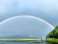 """7月2日傍晚,香格里拉纳帕海上空出现精彩的""""双彩虹""""现象,伴着淅沥沥的小雨,景色动人,引起过往游客驻足观看。图为巨大的双彩虹在纳帕海和山丘之间搭建起一座""""天桥""""。摄/李安琪  文/孙娅蕾  """