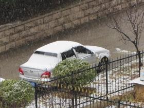 山东烟台降下雨夹雪 防疫人员雨...