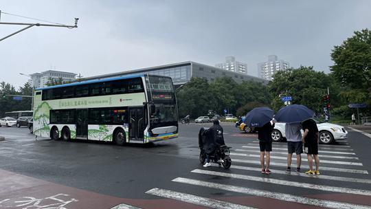北京出现降雨 路面被打湿行人撑伞
